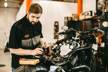 Confident young man repairing motorcycle in repair shop - electronics repair. This bike will be perfect.