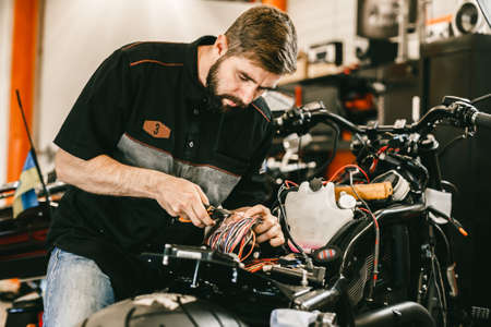 Professional motorcycle mechanic works with electronics, cuts wires. Handsome mechanic working in bike repair shop. Stock Photo