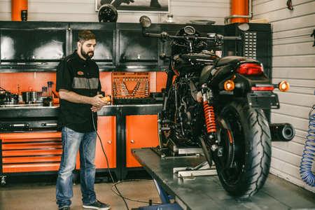 プロのモトのメカニックは、リフトにオートバイを発生させます。上下の自転車修理店でスイッチを押す男。