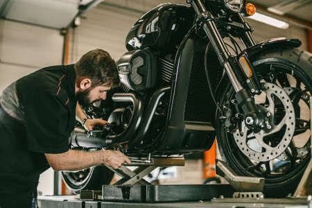 Professional mechanic change the oil in a motorcycle. The sports bike is on the lift.