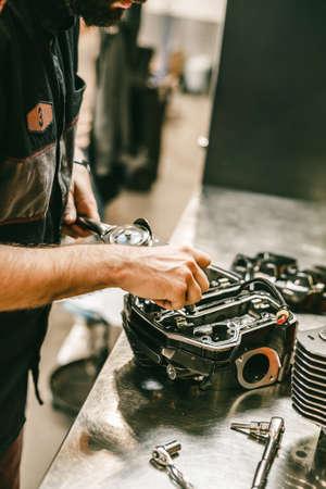 Cropped image of automobile mechanic repairing motorcycle in automobile store. Biker repairing his custom motorcycle