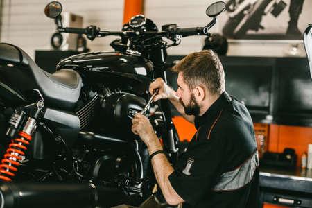 Professionele werktuigkundige schroevendraaier en motor reparaties. Knappe jonge man repareren motorfiets in de reparatie winkel.