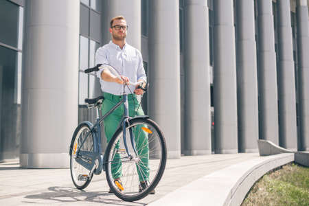 he: Cool young bearded hipster with bicycle on the city street. Smiling casual businessman having a break. He is standing in front of the building next to bike and holding laptop. Stock Photo