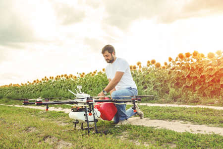 Young man pours fertilizer for irrigation in agriculture drone. Octocopter flight preparation. Stock Photo