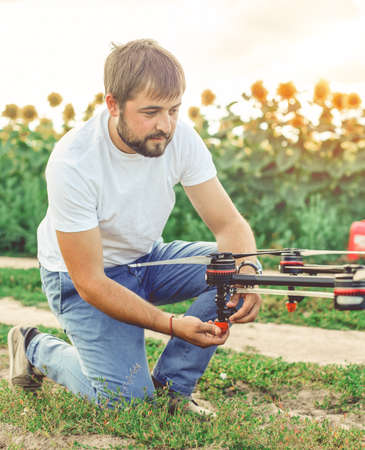 Young engineer preparing agriculture drone before flying on the sunflower field. Banco de Imagens