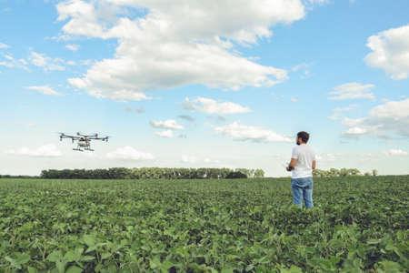 Technicus landbouwer gebruiken wifi computer controle landbouw drone op groene veld. Landbouwhommel op het groene gebied.