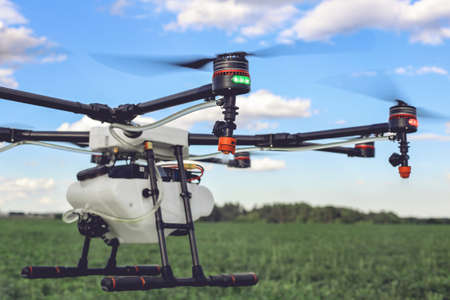 Closeup view of flying professional drone quadrocopter at the green field. Stock Photo