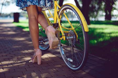Nahaufnahme der weiblichen Beine in den Sommerstiefeln und im gelben Fahrradretro- Rad. Gelbes Fahrrad und schöne weibliche Beine.