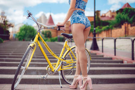 Close up shot of young sexy girl with long nice legs posing with yellow bicycle on city Stock Photo