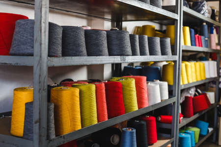 Shelf with large coils of thread. Professional equipment for tailoring in the factory.