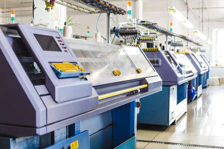 Textile industry with knitting machines in factory. Knitting and weaving machines in textile industry Stock Photo