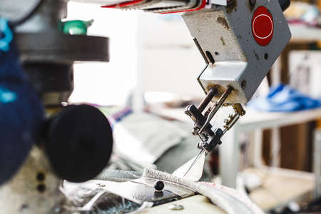 Overlock sewing machine - view on working area and machine front with needle - foreground blanked ot blurry.