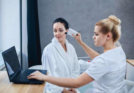 Vrouwelijke arts en patiënt tijdens onderzoek van gezichtshuid. De resultaten van de huidconditie worden weergegeven op de laptop.
