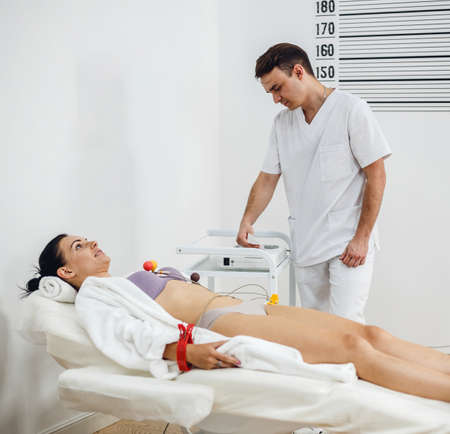 Male doctor with electrocardiogram equipment making cardiogram test to woman patient in hospital clinic.