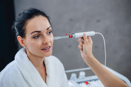 Doctor cosmetologist conducts diagnostics of a condition of a skin of the face of the patient. Picture of nice beautician doing beauty therapy for young woman
