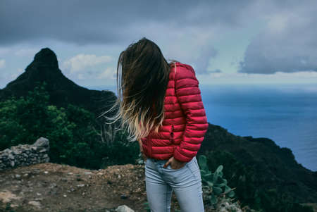 Pretty girl of background of mountain landscape in low key