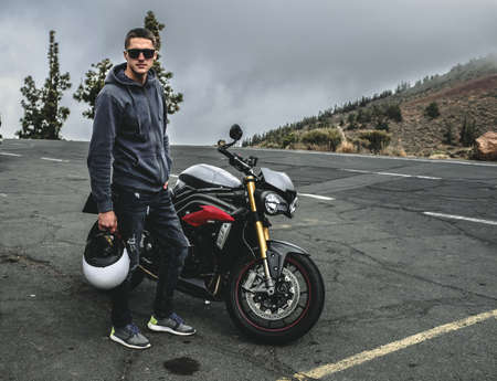 Rider stand on a mountain next to motorcycle Stock Photo