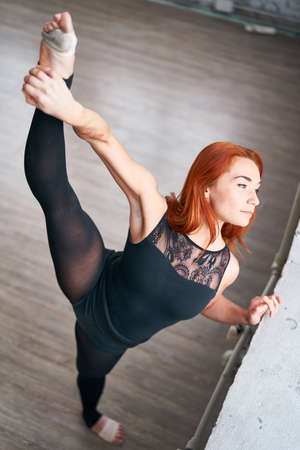 Girl dancer doing stretching near the window in white dace hall in loft style