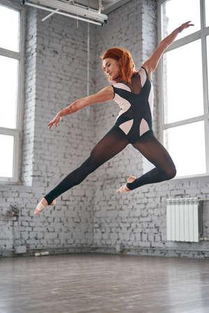Beautiful ballet dancer posing in dance studio. Charming young dancer performing in the studio