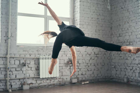 The young attractive modern ballet dancer in black jacket jumping over urban background.