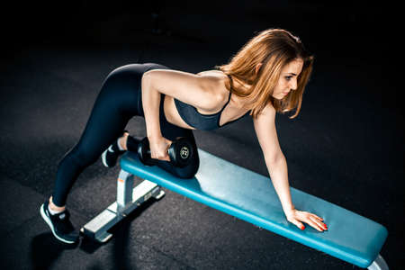 Girl doing triceps exercise with dumbbells in gym Stock Photo