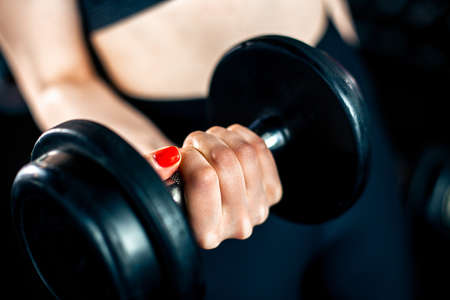Girl doing bicep exercise with dumbbells in gym