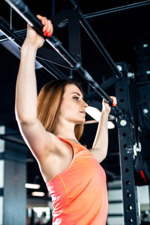 Pretty girl do pull-ups in the gym