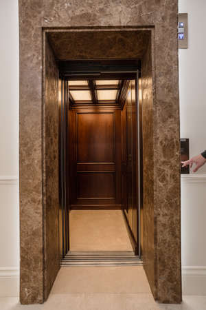 Wooden lift in business office building. Man push the button