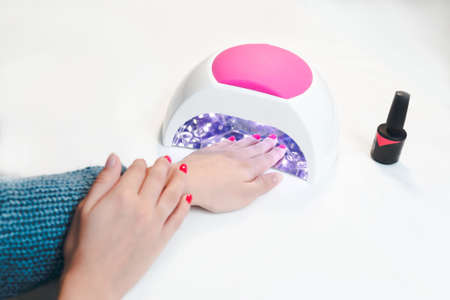 Woman hand inside UV lamp for nails on table close up.