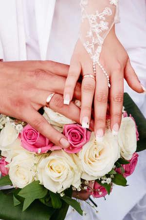 honeymooners: Hands honeymooners on the wedding bouquet of roses, wedding rings on fingers Stock Photo