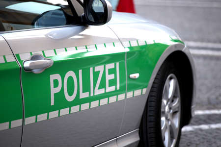 Silver police patrol car with green sticker - Photo