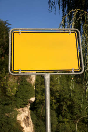 Yellow road sign on a background of trees - Photo