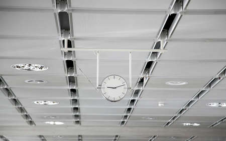 Hanging white clock at the big train station - Photo 免版税图像