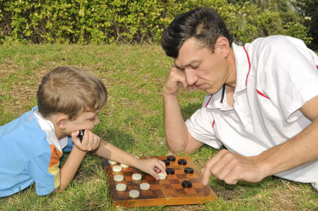 Father and the son play checkers(blocks) on the nature photo