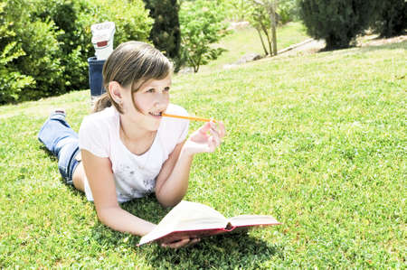 reverie: The girl has fallen into a reverie  above the book Stock Photo
