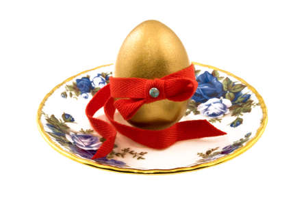 testicle: Golden testicle on a plate decorated with red ribbon Stock Photo