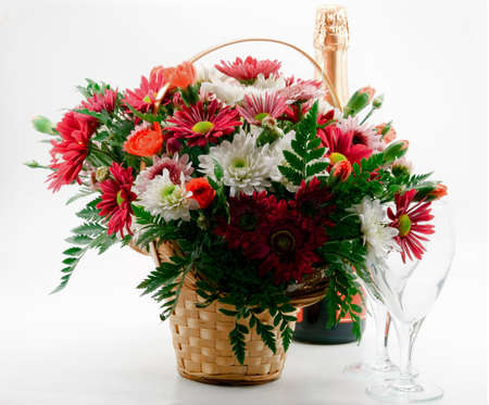 A gift, a bouquet of flowers in the basket a bottle of champagne and two glasses photo