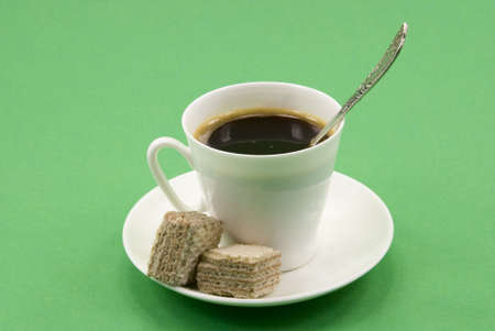 A cup of black coffee with a spoon and waffle cubes photo