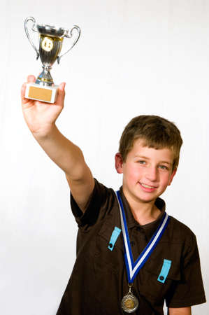 The boy won a competition in chess, and happily holds in his hand a cup photo