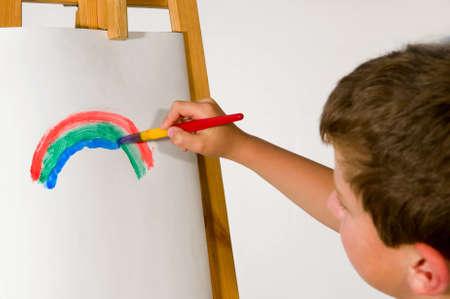 大きめのブラシを紙に描く少年虹