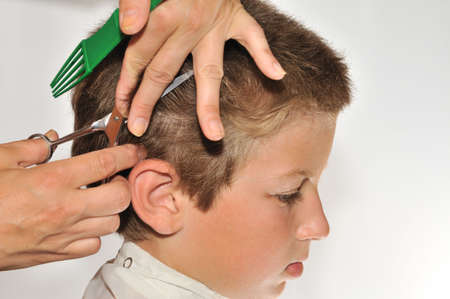 Hairdresser clipper boy harboring his cloak from falling hair photo