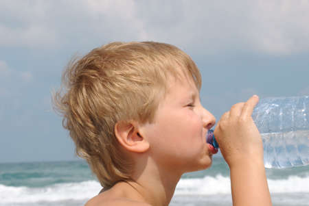 Boy drinking water from a bottle on a hot day photo