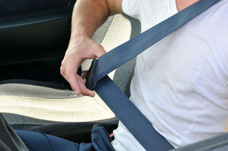 The driver sits in the car and lays down the safety-belt photo
