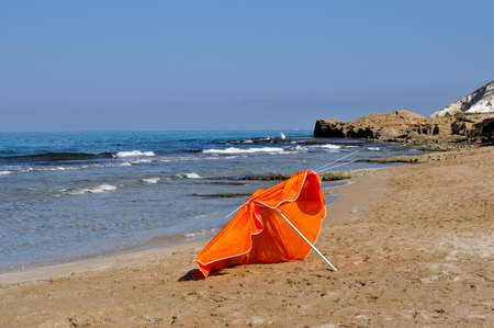 Thrown out, a broken umbrella at the end of the swimming season. Banco de Imagens