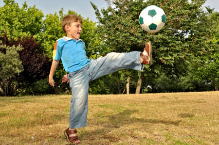The boy from all force kicks the ball with his foot photo