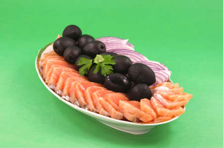 Salmon chopped on flat pieces adorned with black olives and onions