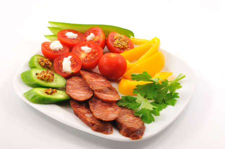Spicy Hungarian sausage with chopped ovoshami lies on a plate Standard-Bild