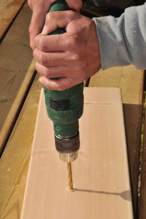 drilling holes in the boards for cladding wooden house  photo