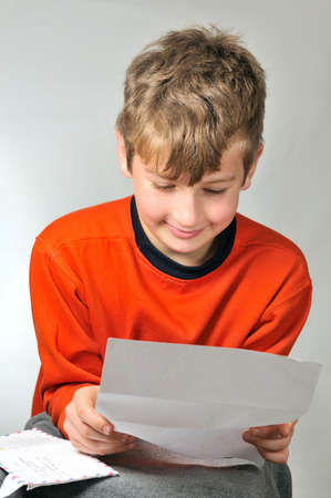 addressee:  boy reads a letter he received from friends  Stock Photo