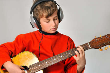 boy at a rehearsal with headphones, playing guitar Imagens - 6096379
